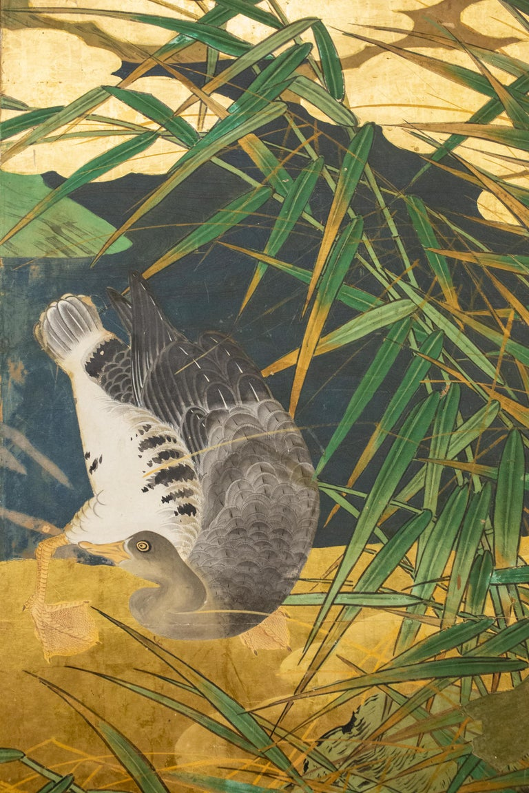 With a banana leaf palm on the left, at water's edge with geese. Perhaps a scene from the southern islands. Mineral pigments on mulberry paper with gold leaf and a silk brocade border.