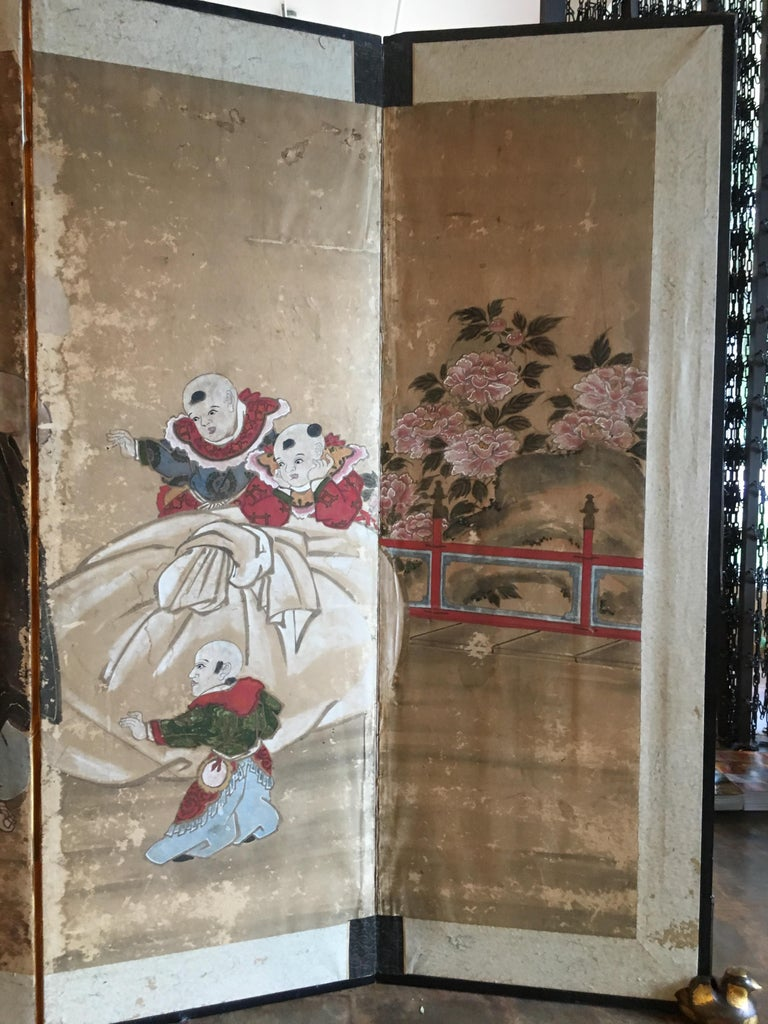 A delightful Japanese six panel painted paper screen featuring the beloved figure Hotei, Edo Period, early 19th century. 