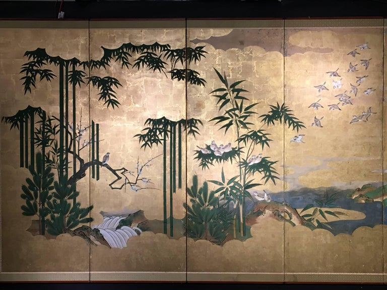A beautiful and elegant Japanese Edo period six-panel painted screen, byobu, 18th-19th century. The screen featuring a flock of sparrows descending from billowing golden clouds to roost in a bamboo grove. A rushing white water stream flows through