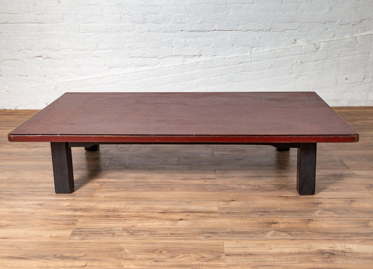 A Japanese Taisho period coffee table from the early 20th century, with Negora lacquer and black legs. Born in Japan during the first quarter of the 20th century, this charming coffee table was originally found in a coffee shop (you will indeed