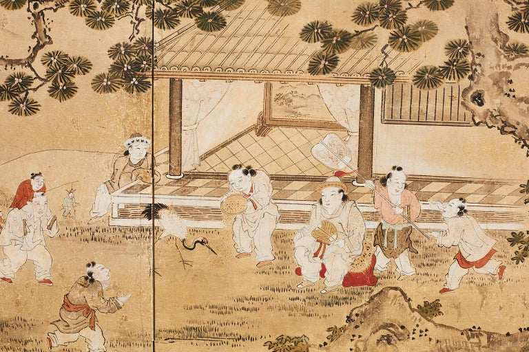Exquisite Japanese two-panel Meiji period painting made in the Kano school style. Features a lively scene of children playing in a yard under an ancient pine tree near a home. The painting is surrounded by gold leaf clouds and set in a later