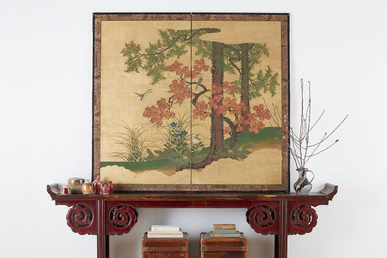 Late 19th century Japanese Meiji period two-panel screen depicting an autumn landscape with Japanese song birds. The screen features a Buddhist pine or Maki tree and a Japanese maple or momiji tree. Painted with ink and color over gold leaf squares