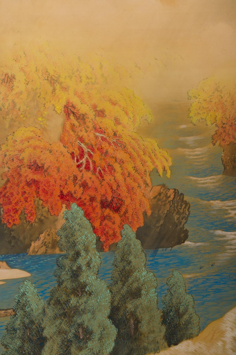 Japanese two-panel screen, autumn colored canyon in the mist, early Showa period (1926-1989) painting of a river running through a canyon with fall colored trees above a sandy river bank with flying swallows. Beautiful colors and lively landscape,