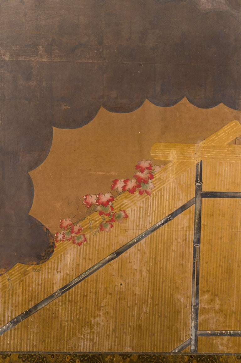 Edo period painting (1614-1868) of an autumn garden scene with a wood vine on a bamboo fence and silver clouds. Mineral pigments on paper with a silk brocade border.