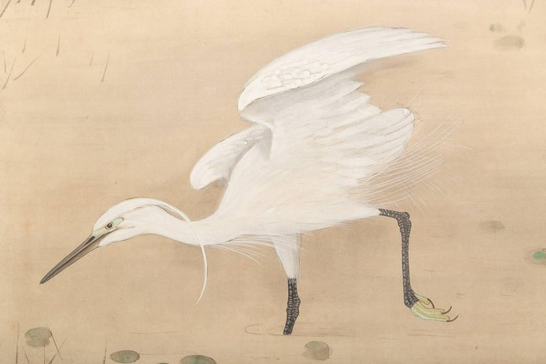 Japanese Screen painted with Heron In Water Lily Pond Under Willow.  Meiji period (1868 - 1912) painting of a heron at pond's edge.  Painted in mineral pigments on mulberry paper.  Artist's seal reads: Yoshi Take / Houshou.  One of a pair with