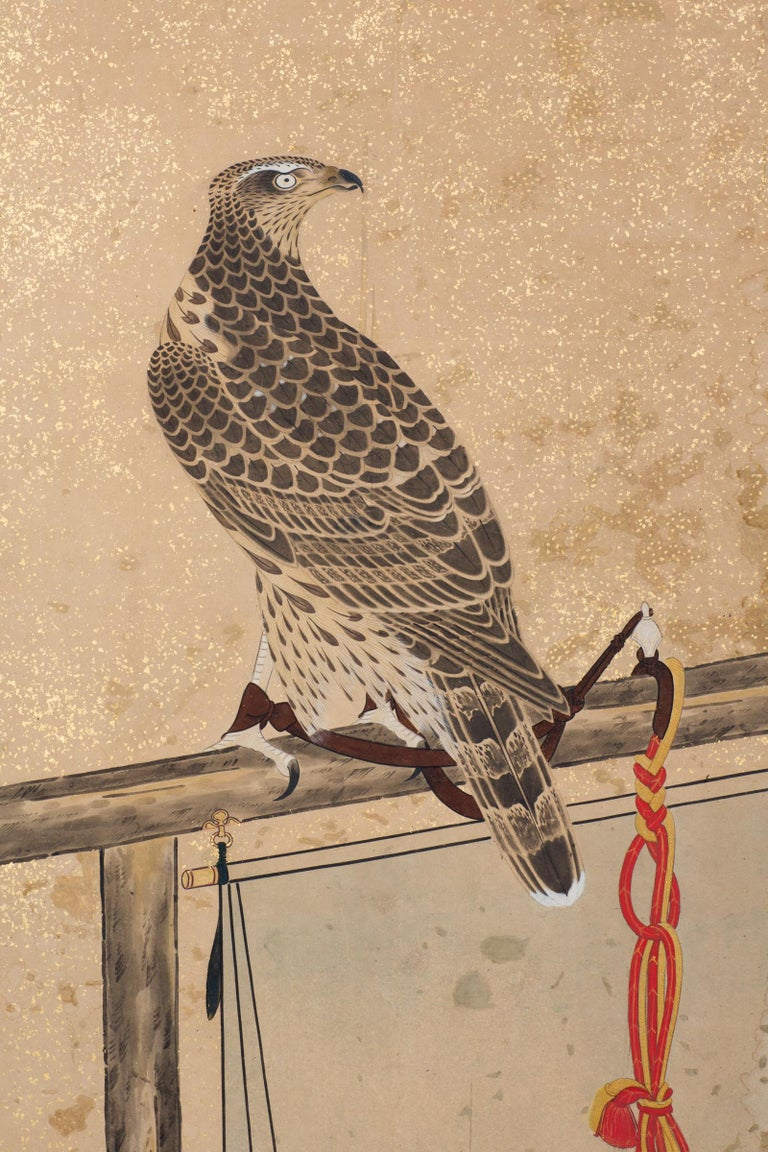 Late Edo period (1614-1868) painting of two falcons with silk knotted tethers resting on perches. Ink on paper mounted on gold with gold flecks, a hand painted checkerboard pattern, and a silk brocade border. Painting is circa 1800, mounted on board