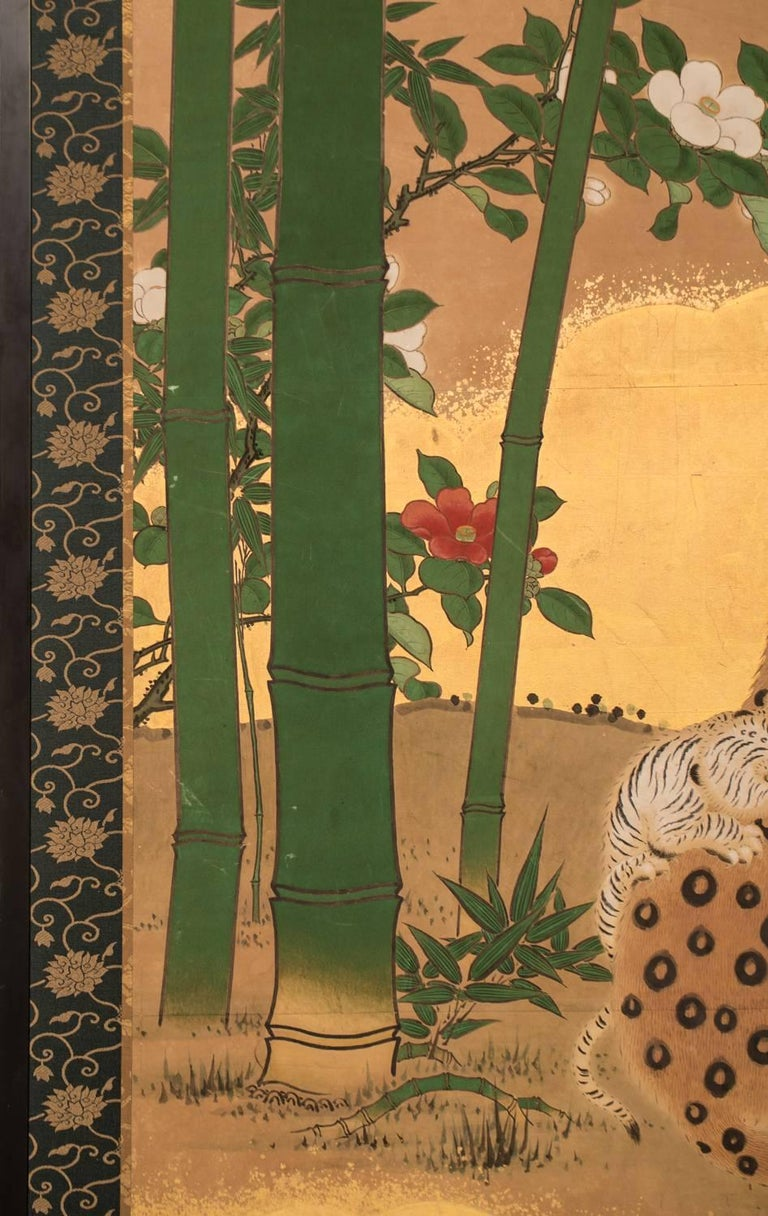 With gold clouds on gold leaf with camellia on river's edge. In history, Japanese artists did not see leopards or tigers in real life because the animals were not native to Japan, they lived in China. Artists were only exposed to skins and stories