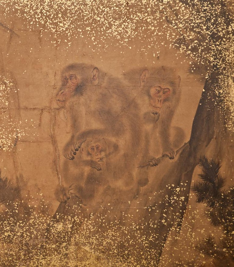 Japanese Two Panel Screen: Troop of Monkeys in a Tree.  Edo period (Mid 19th century) ink painting (sumi-e) of interactions between a group of Japanese macaques.  Ink and minimal pigments on mulberry paper with gold dust and a double border in gold