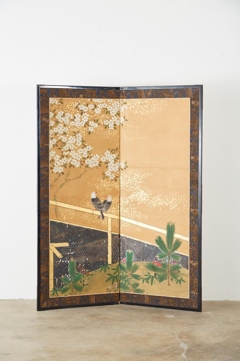Serene Japanese two-panel Showa period screen depicting a pair of birds resting on a bamboo fence. Above the birds is a white blossoming Sakura cherry tree and bright green pine saplings below. Made in the Nihonga school style. Ink and color