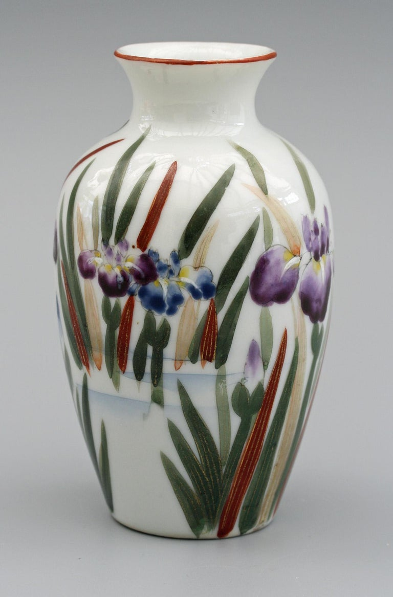 A very fine vintage Japanese porcelain vase, probably Arita Fukagawa, hand painted with a bird amidst flowering iris's dating from the first half of the 20th century. The small bulbous shaped vase has a narrow and short trumpet shaped top and is