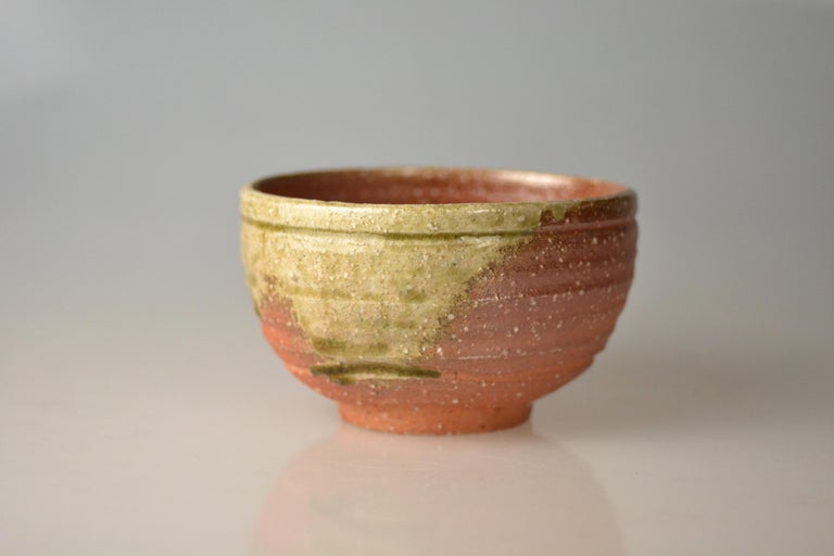 Traditional, hand-thrown tea bowl for matcha with ash glaze from wood firing. Takahashi Rakusai IV (1925) is one of Japan's grand masters of traditional pottery who specialized within his family business on Shigaraki ware. Shigaraki ware is a sandy