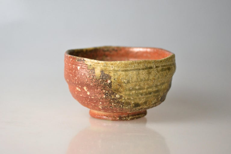 Traditional, hand-thrown tea bowl for matcha with ash glaze from wood firing. Takahashi Rakusai IV (1925) is one of Japan's grand masters of traditional pottery who specialized within his family business on Shigaraki ware. Shigaraki ware is sandy