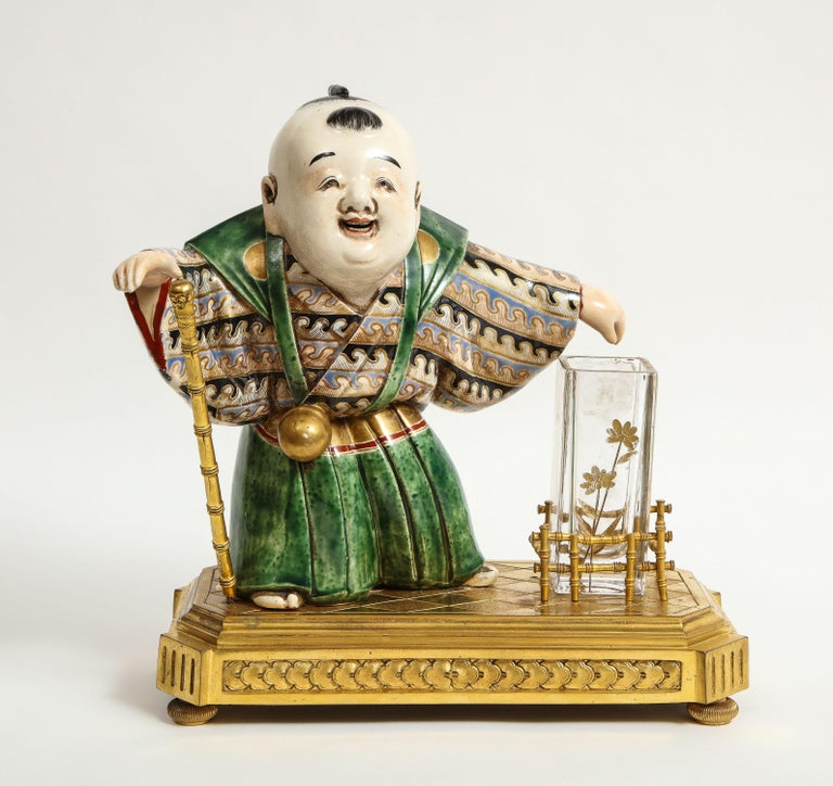 Japonisme French Ormolu, Japanese porcelain and glass centerpiece, circa 1870. Attributed to L' Escalier de cristal, Paris.  Depicting a Japanese porcelain boy, holding a bronze staff in his hand, with a glass flower vase inserted in a bronze bamboo