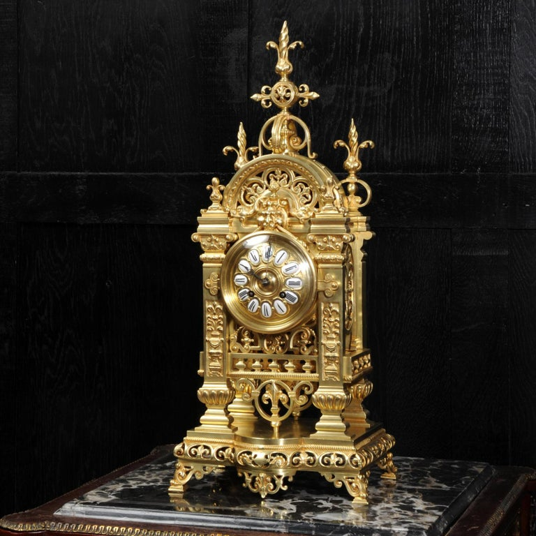 A superb antique French clock by Japy Frères, circa 1870. It is very well made in gilt bronze in the Gothic style. The case is architecturally formed of 4 gothic columns supporting fretted tracery panels allowing the pendulum to be seen gently