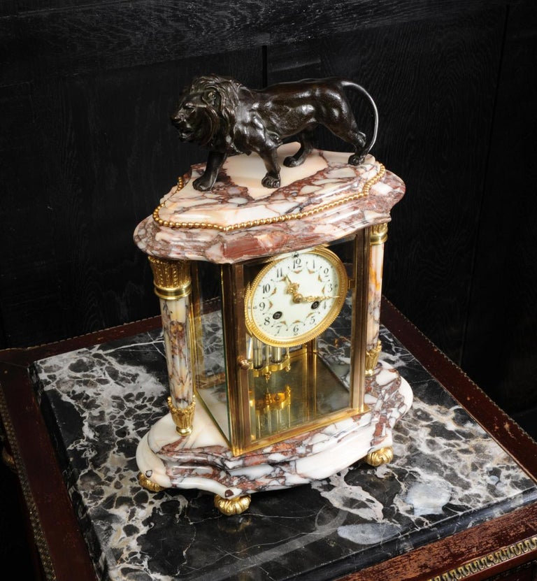 A beautiful antique French specimen marble library four glass or crystal regulator clock by the renown maker Japy Frères, circa 1880. It is classical in style with two reeded acanthus troche columns and a well modeled bronze lion standing proudly to