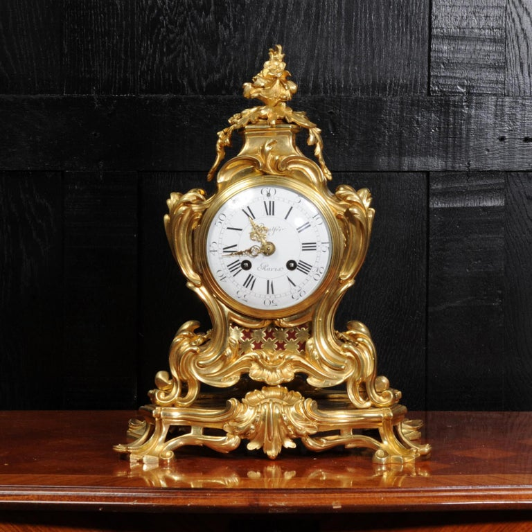 A stunning original antique French Rococo clock, circa 1870. It is beautifully sculptured with finely finished scrolls, curves and acanthus leaves in finely gilded bronze. Panels backed with red fabric lighten the design and the rear door is glazed