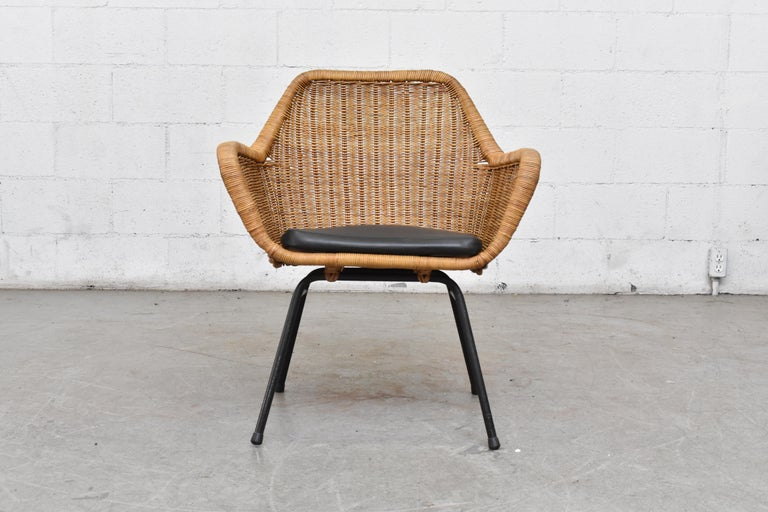 Jaques Adnet style midcentury rattan bucket chair in original condition with original black skai seat cushion. Black enameled metal frame. Nice original condition with minimal wear.