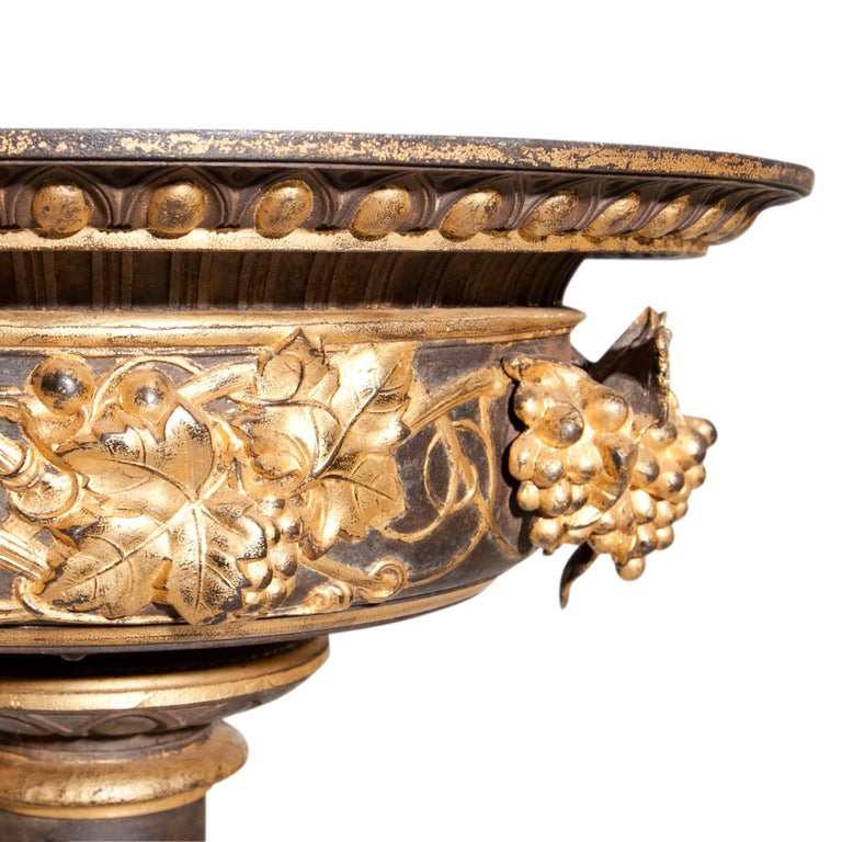 Large cast iron jardinière on a round stand with a square plinth, decorated with acanthus leaves. The basin is decorated with plastic grapes and vines in relief on the wall. Partly raised in gold.
