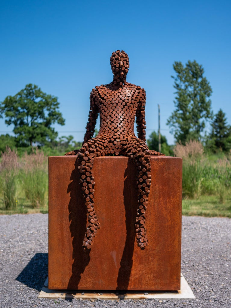 A seated figure reclines atop a steel cube in this outdoor sculpture by Mississippi artist Jason Kimes. Made of welded coin-sized discs of steel, the figure's shell is slightly transparent. The work that has taken on a weathered, rusted patina