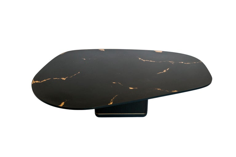 The sleek and striking curved jasper coffee table features a charred black oak base with blackened steel and bronze banding, and a black marbled rose bronze encased in resin tabletop with blackened steel banding.  Dimensions as shown: L 50 in. / W