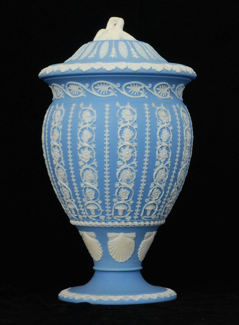 A finely worked vase in solid pale-blue jasper, engine turned and decorated with arabesque designs; the lovebird finial finishes the composition very nicely.