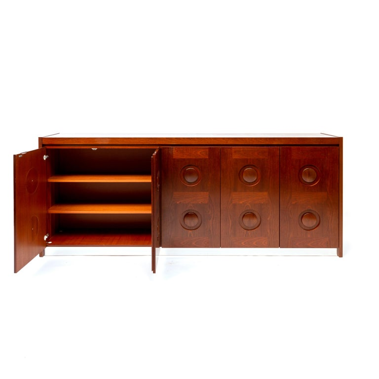 Minimalist/Mid-Century Modern/Brutalist piece that fits well in an eclectic chic interior. This large sideboard with geometric doors is made in Belgium in the 1970s. The credenza shows a round pattern on its doors. This cabinet looks fantastic, with
