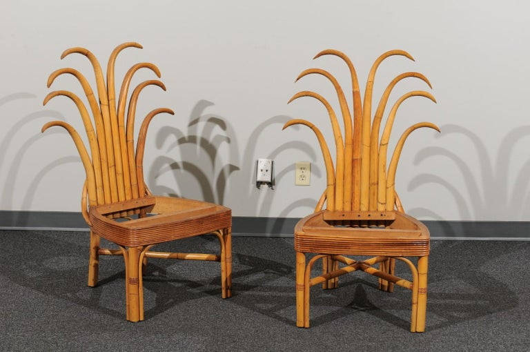 An absolutely majestic set of twelve (12) custom made palm frond style dining chairs, circa 1950. Exceptionally conceived and crafted rattan and hardwood construction with a magnificent back detail. Stout, rigid and comfortable - built for heavy