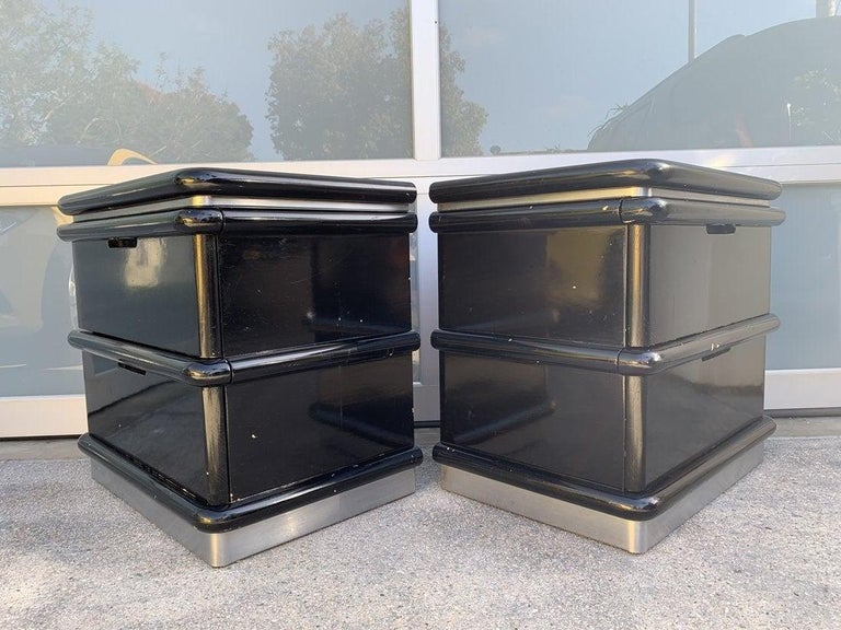 Beautiful pair of nightstands designed by Jay Spectre in the late 1970s or early 1980s. The nightstands are freshly refinished in a high gloss black lacquered finish, the plinth base is embossed with brushed chrome, they each have two large drawers