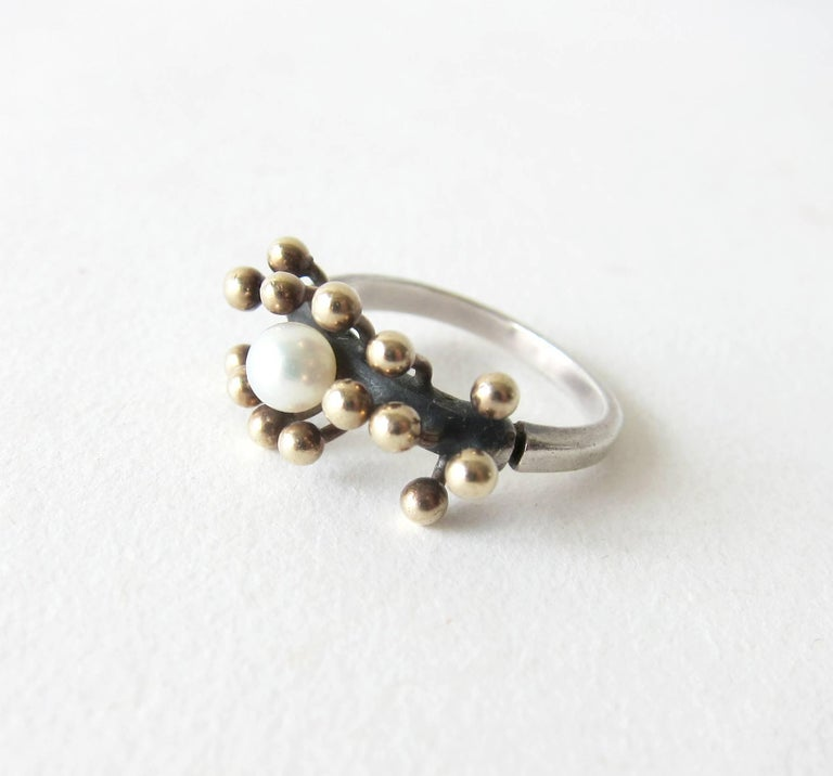 Sterling silver ring with 18k gold spores surrounding a freshwater pearl created by Jay Tuttle of San Jose, California.  Ring is a finger size 6.5 to 6.75 and is signed Tuttle, Sterling.  An unconventional alternative to a modern day engagement