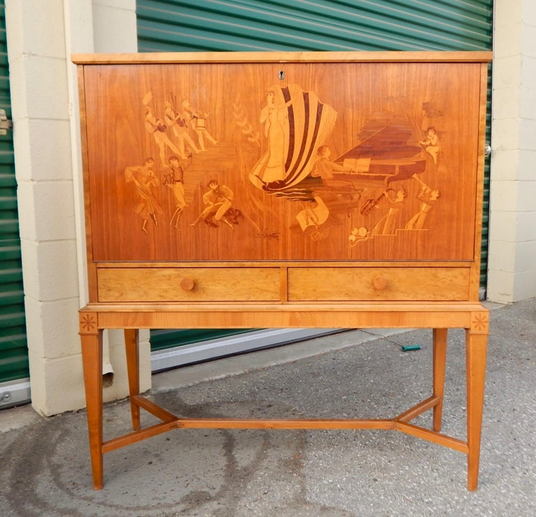Swedish art deco era drop front dry bar. With intricate inlay depicting jazz age musicians and scenes. Designed by Birger Ekman for Reiners Mobler in Mjölby, Sweden in the 1930's. In great original condition in original finish. Some signs of