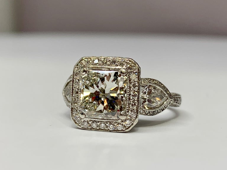 This breathtaking platinum three stone ring designed by JB Star holds a gorgeous center radiant-cut diamond weighing 2.10 carats. The quality of the center stone is approximately H/VS1. The mounting hold a total diamond weight of 1.60 carats,