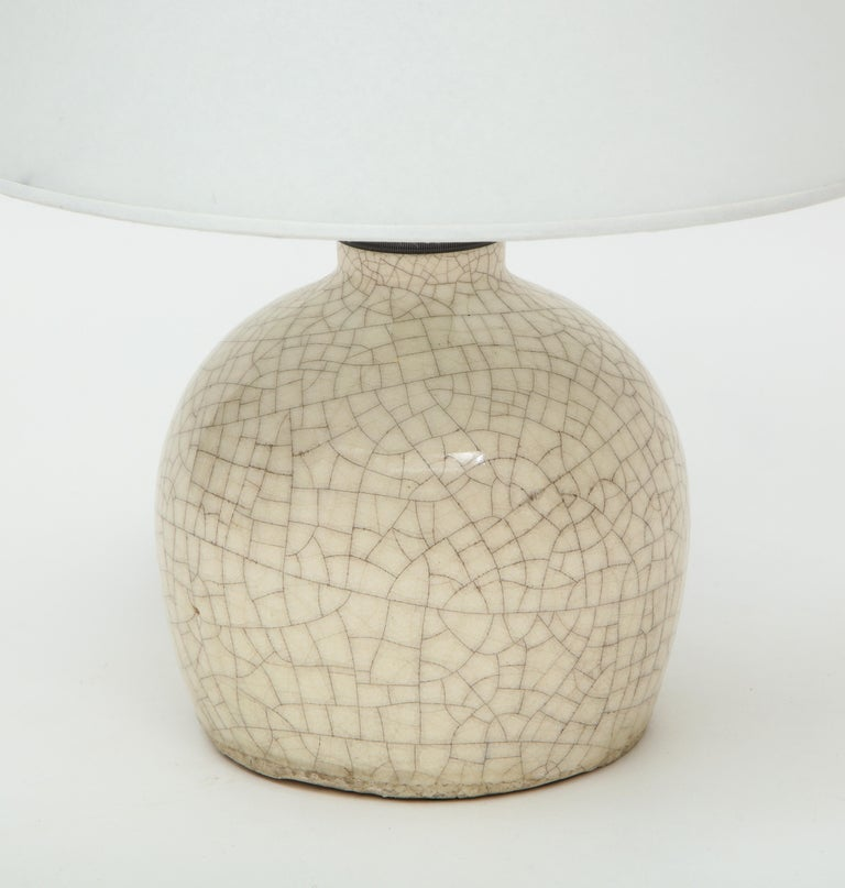 Jean Besnardcrackle glaze unusually shaped ceramic lamp with custom parchment shade, France, c. 1926, signed Ceramic, Bronze, Parchment Measures: Height 1014.5 Diameter 5.75 in. Shade: 11