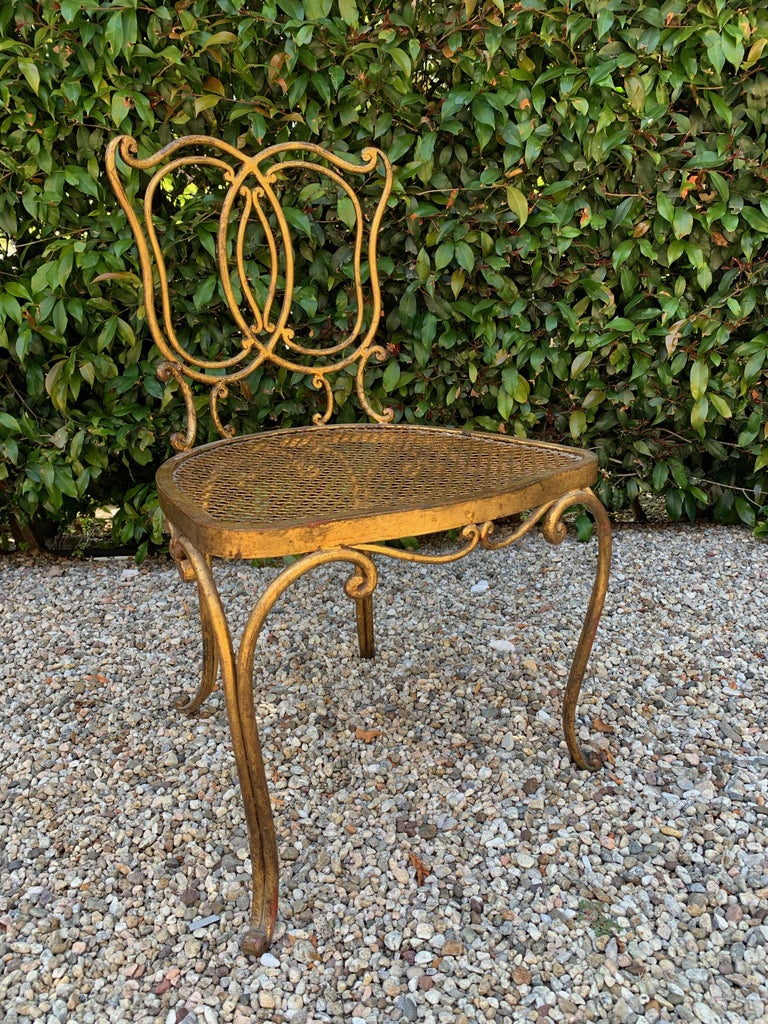 Jean-Charles Moreux gilt French vanity stool chair, a sexy French, petite chair in gilt iron, perfect for the dressing room, bedroom or vanity. With a leopard or solid white, or bone cushion the piece would a comfortable personality all its own.