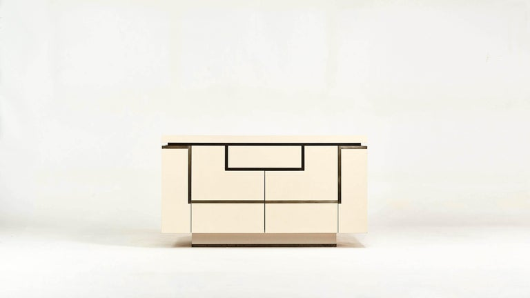 Ivory lacquered wood sideboard enhanced with brass, by designer Jean-Claude Mahey for Roche Bobois. Opening with two side doors revealing bar, and 2 doors and 1 drawers in front. Small traces of use, good overall condition, circa 1970.