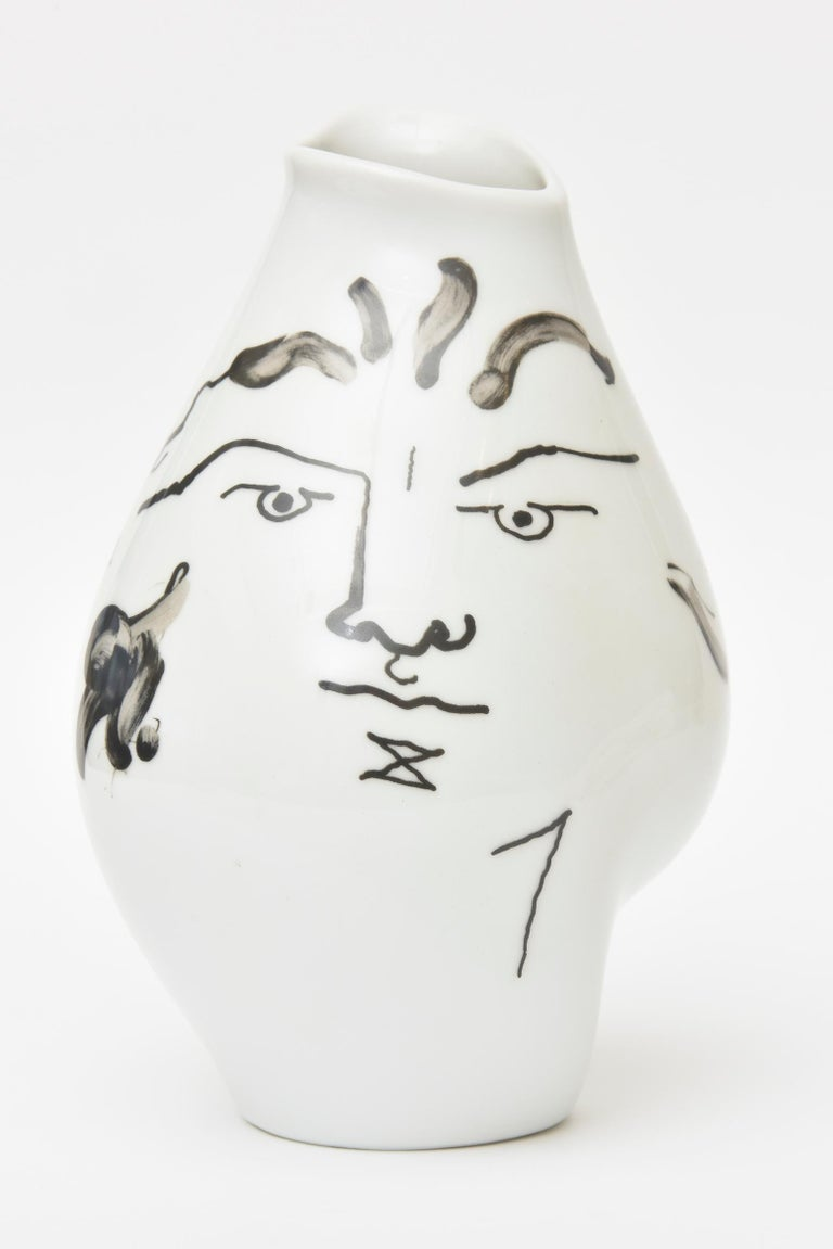 This wonderful glazed porcelain tetes face vase originally designed in 1952 by Jean Cocteau and was produced in the early 1970s by the Classic Rose Rosenthal Group, Germany. The freeform design of abstract facial motifs and ovoid irregular shape of