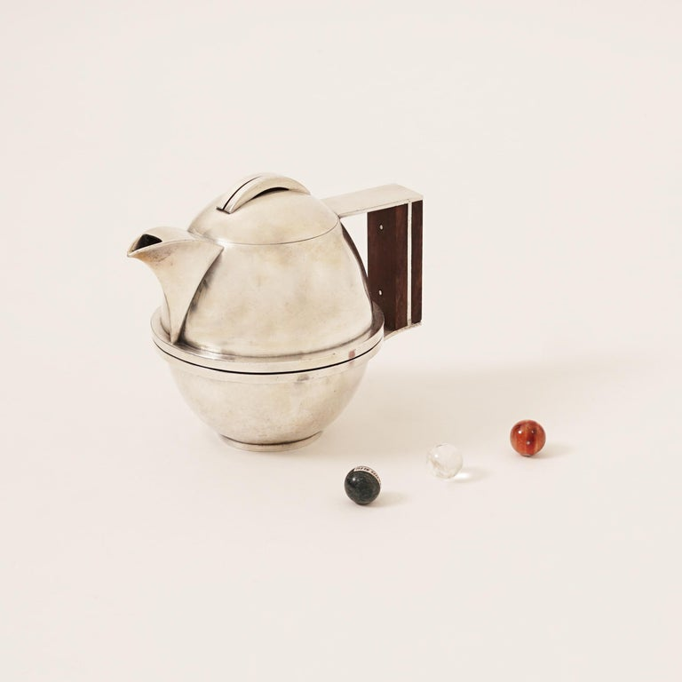Jean Despres (1889-1980) Tea-Pot, circa 1930 Tin, base in hammered Tin, animated with spherical stipes and angular Madagascar Ebony Wood handle. Spherical Hinged cover with two silver stripes.  Signature incised