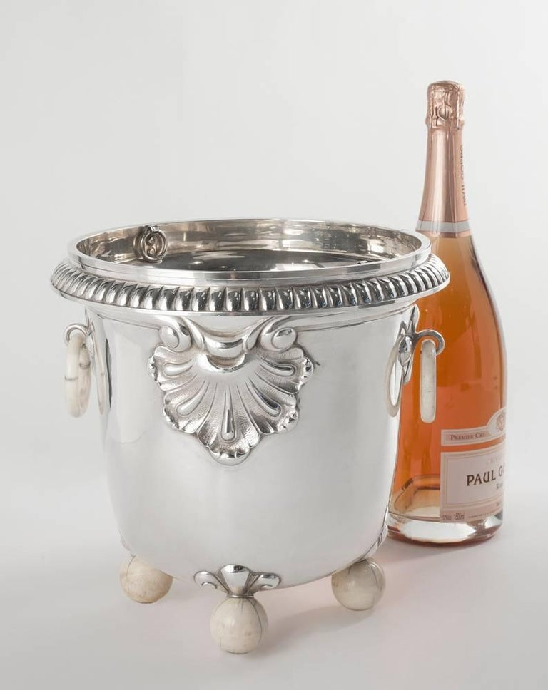 This remarkable wine cooler by the eminent Art Deco silversmith Jean Puiforcat features an elegant, sloping shape, scalloped embellishments, and bone handles and feet.