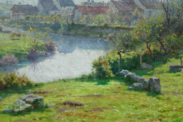 A wonderful oil on canvas by Jean Ferdinand Monchablon whose work was influenced by both the Barbizon School and Impressionist movement. The piece depicts a French village landscape - cattle grazing in a field next to a river on a warm summer's day