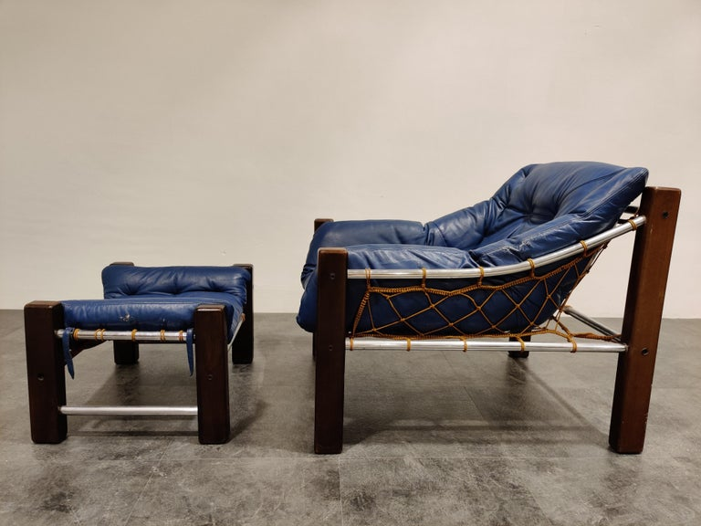 Stunning midcentury leather armchair with ottoman in a beautiful blue leather upholstery (original).  This unique armchair sits very well and is the typical style of Jean Gillon with the fishnet style design.  Good original condition, minimal