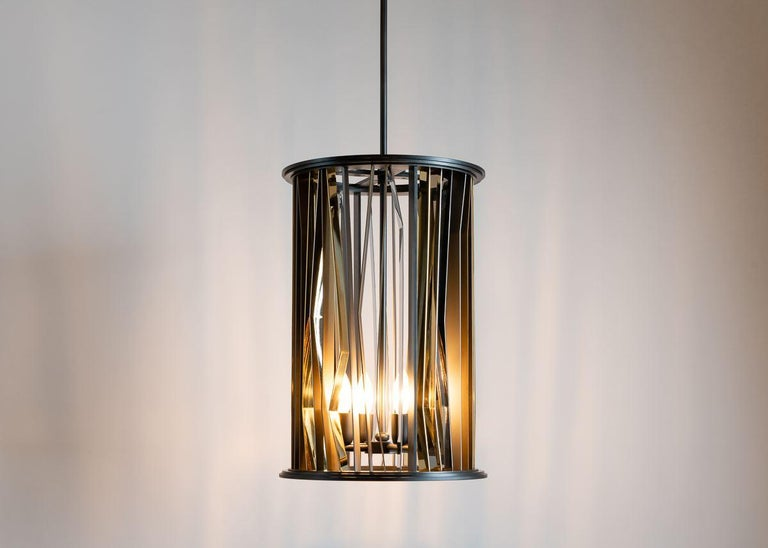 This pendant, available in three sizes—the largest an ellipsis, the two smaller sizes cylinders—is made of gunmetal steel alternately patinated or polished to a satin soft finish. The gleaming brass strips that adorn the chandelier pay tribute to