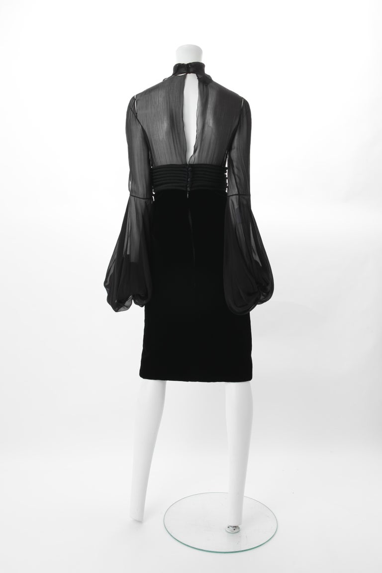 Jean-Louis Scherrer by Stephane Rolland Black Dress w/ Rouleux Waistband, A/W 2003. Knee length black dress with velvet skirt and turtleneck sheer silk bodice featuring long bishop sleeves. Dress also features a Rouleux high waistband and bow tie