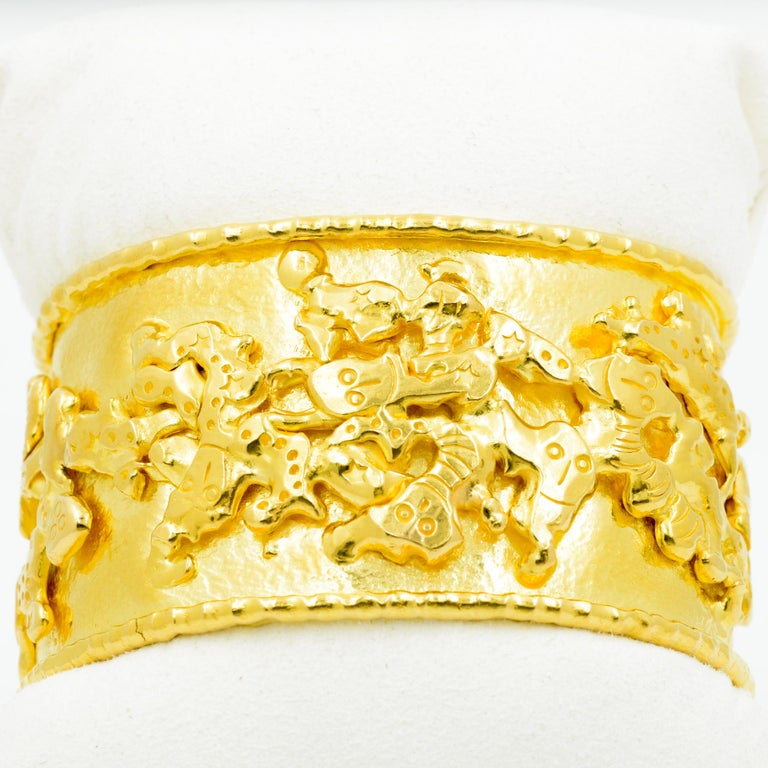 By designer Jean Mahie, the Charming Monsters cuff is crafted from 22 karat yellow gold with playful stylized figures adorning the surface. The cuff measures 1.25 inches wide.