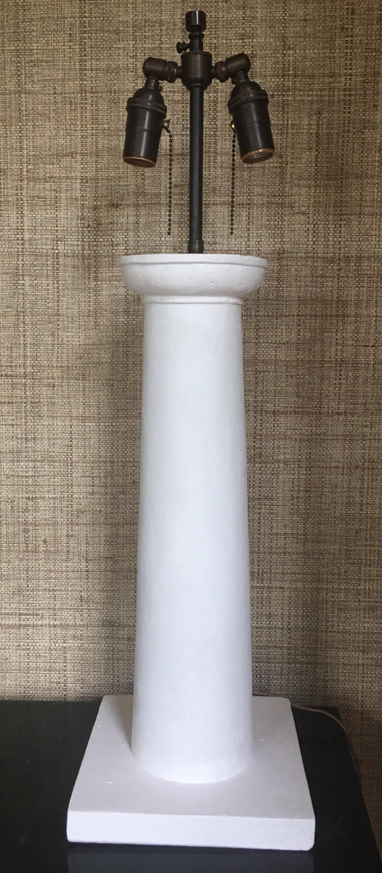 Jean-Michel Frank style Colonne matte white heavy weight molded plaster table lamp. Bronzed metal accents feature two double articulating standard sockets and an adjustable height shade extender finial. Extra long 8 foot fabric covered cord. Custom