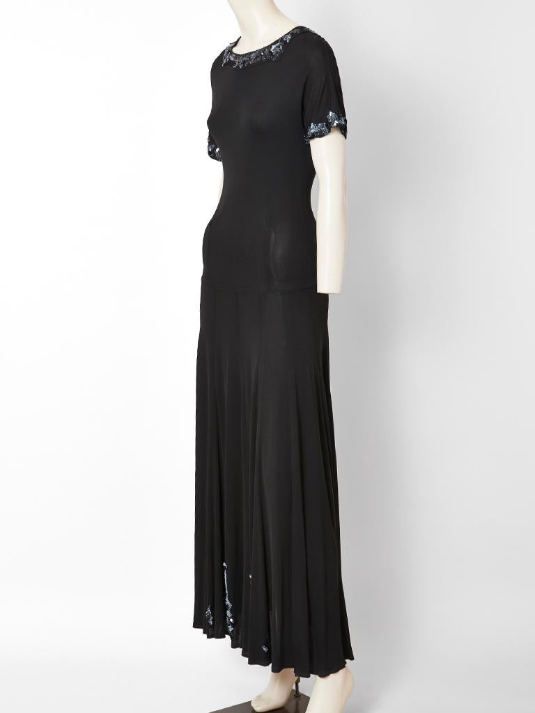 Jean Muir, black jersey, maxi dress having a fitted dropped waist bodice and a gored skirt. Dress has a rounded neckline, short sleeves and iridescent blue sequin embellishment at the neckline and sleeve edges. There is vertical sequined