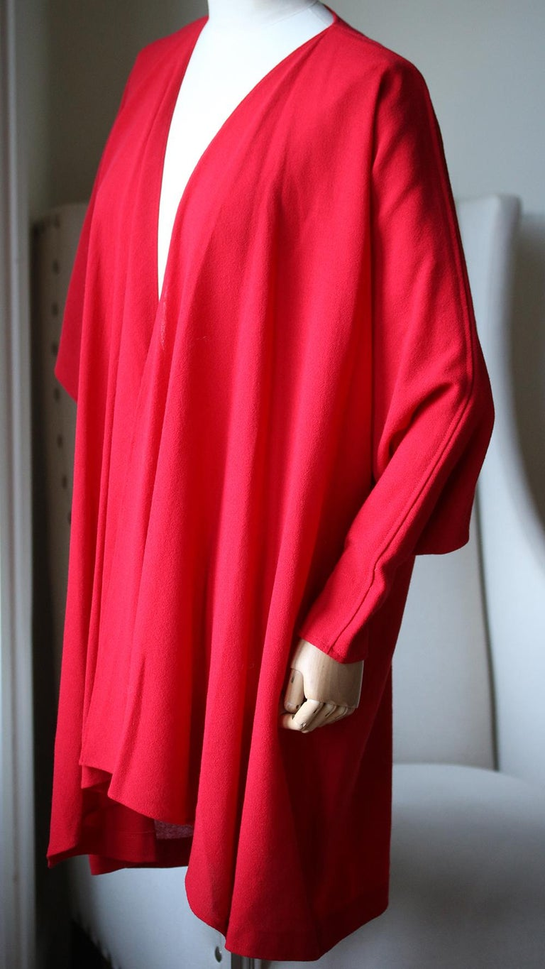 Lovely vintage piece from Jean Muir, an iconic, collectible designer. The finest crepe in bright red, with draping front detail, wide cuff, hanging to the hips. Simple tailoring that has stunning details. 100% Viscose.  Size: UK 10 (US 6, FR 38, IT