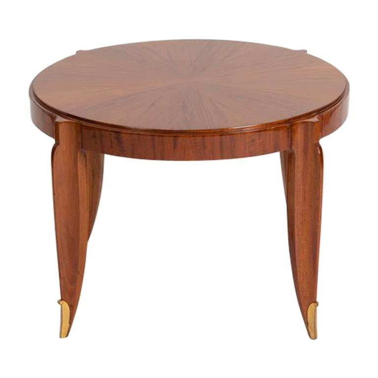 Stamped: Groupe des ébénistes d'art Paris  A well-proportioned piece by the Deco great Jean Pascaud, this mahogany table features a lovely round top and subtly curved legs which terminate in curled bronze sabot.