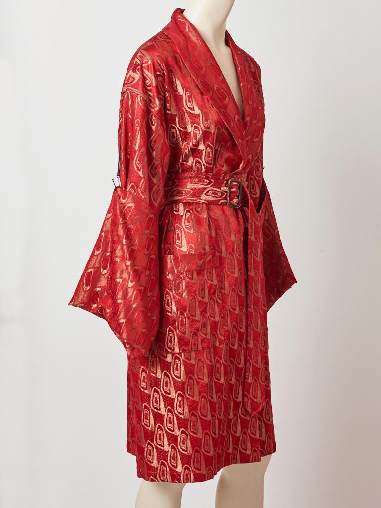 Jean Paul Gaultier, red and gold brocade belted kimono style coat/robe having a shawl collar, deep patch pockets, and extra long sleeves that can be anchored to the shoulder with a metal like detail. Belt buckle is oversized having a bronze tone