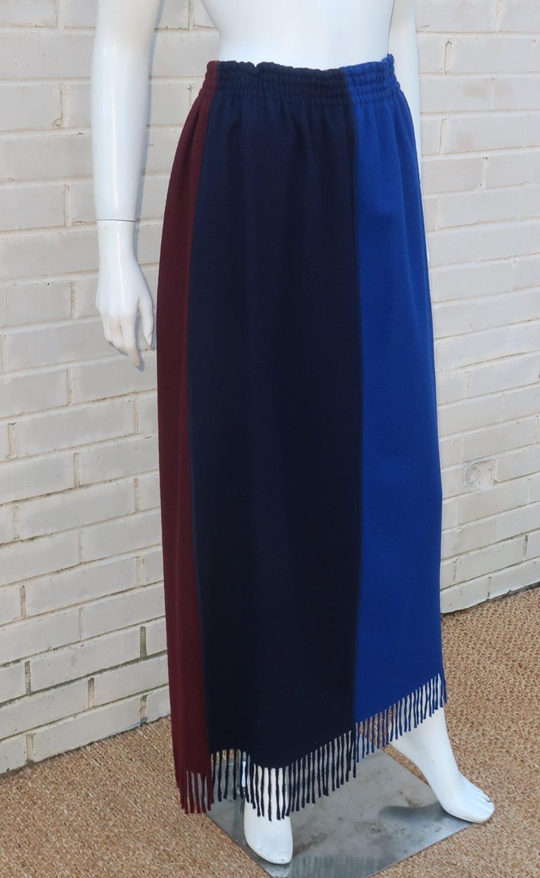 Jean Paul Gaultier pull on wool skirt with a four panel color block design including shades of bright blue, midnight blue (almost black), brown and teal.  The maxi length and fringe hemline provide both a stylish and cozy look especially when paired