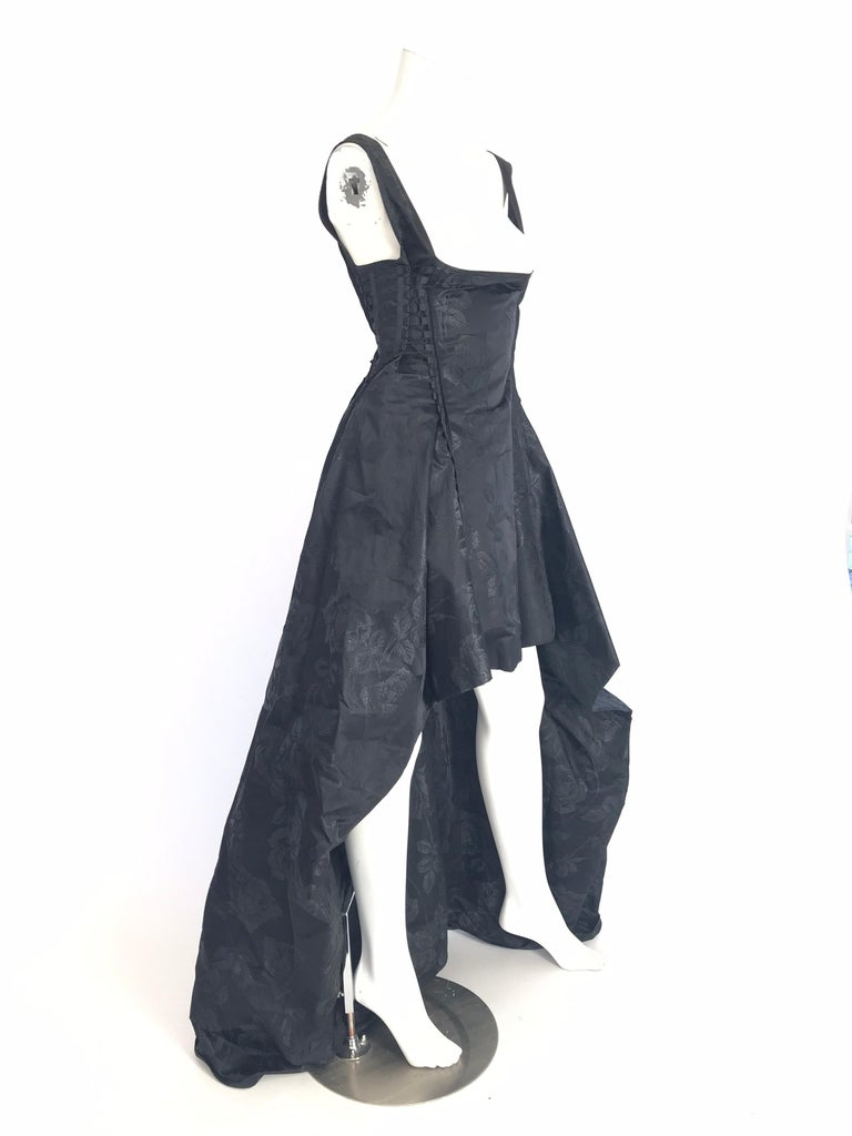 Jean Paul Gaultier black brocade evening dress with floral pattern throughout, lacing at sides, high-low hem and zip closure at back.  Silk blend. Condition: Excellent  Bust: 28