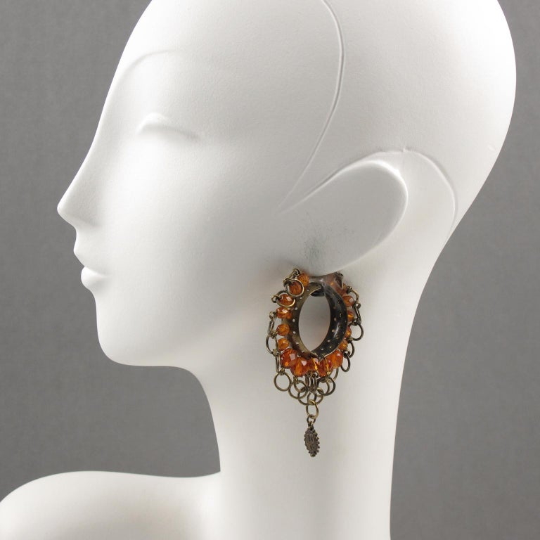 Lovely Jean Paul Gaultier Paris gothic inspiration signed clip-on earrings. Large hoop shape in gilt metal with aged patina ornate with metal rings and orange glass faceted beads. Dangling